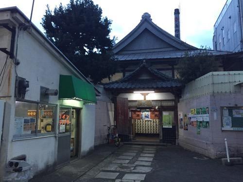東京都荒川区の銭湯・玉の湯の正面入口と煙突とコインランドリー(写真左手)