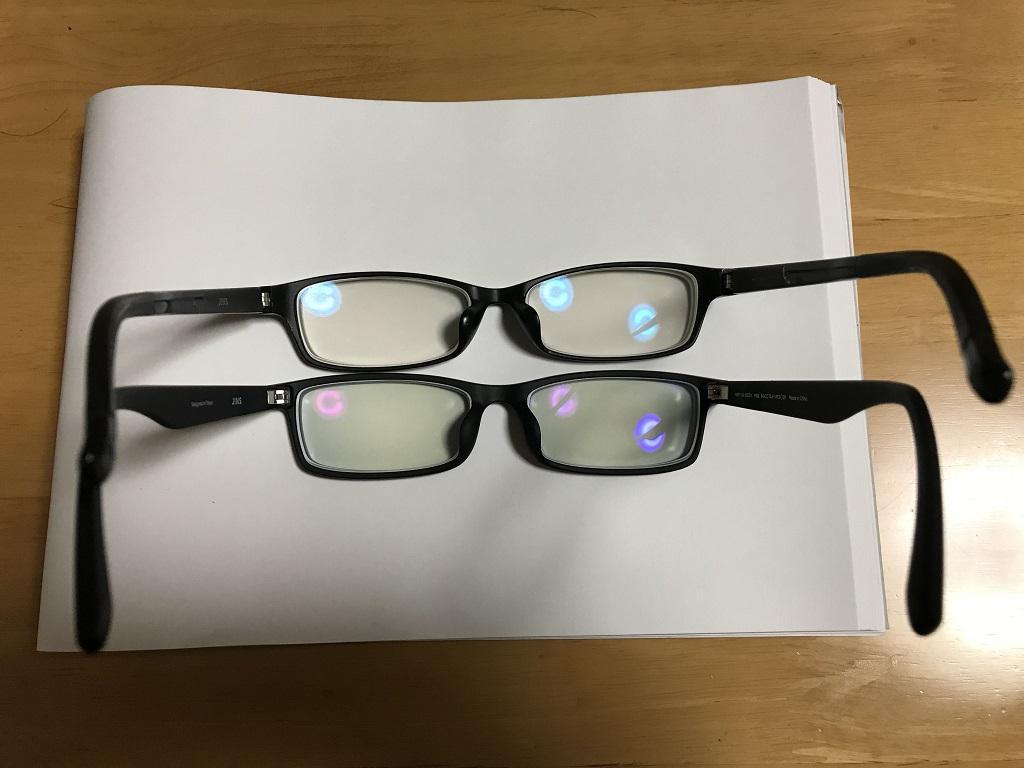 ジンズで購入したブルーライトカットレンズの眼鏡2つ(上:13%カット、下:40%カット)。裏側より。白い画用紙の上にて。