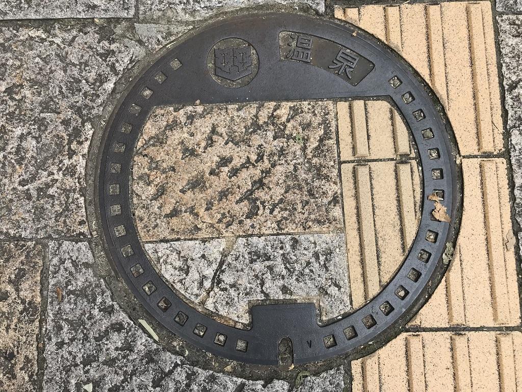 愛媛県松山市のマンホールの蓋 - 道後温泉本館前の点字ブロックと一体化した歩道上のマンホールの蓋